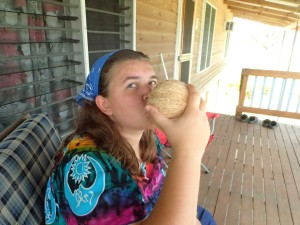 Rachel drinking from a green coconut