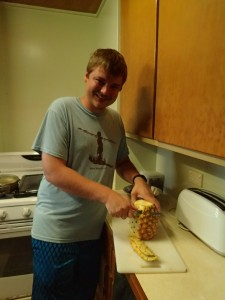 Josiah cutting up a pineapple